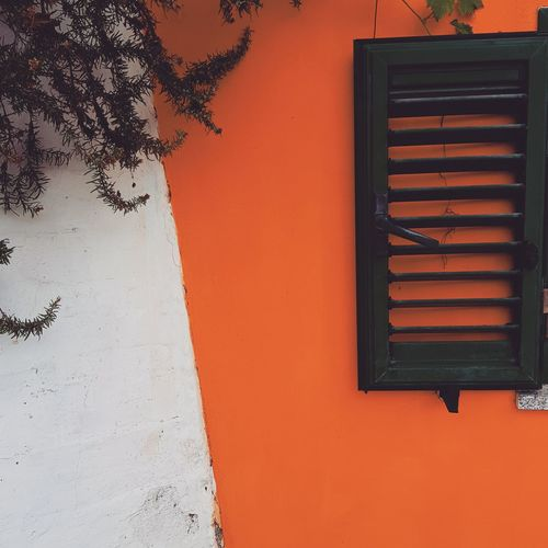 Close-up of window on orange wall