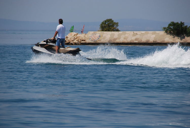 Man riding jet boat in sea