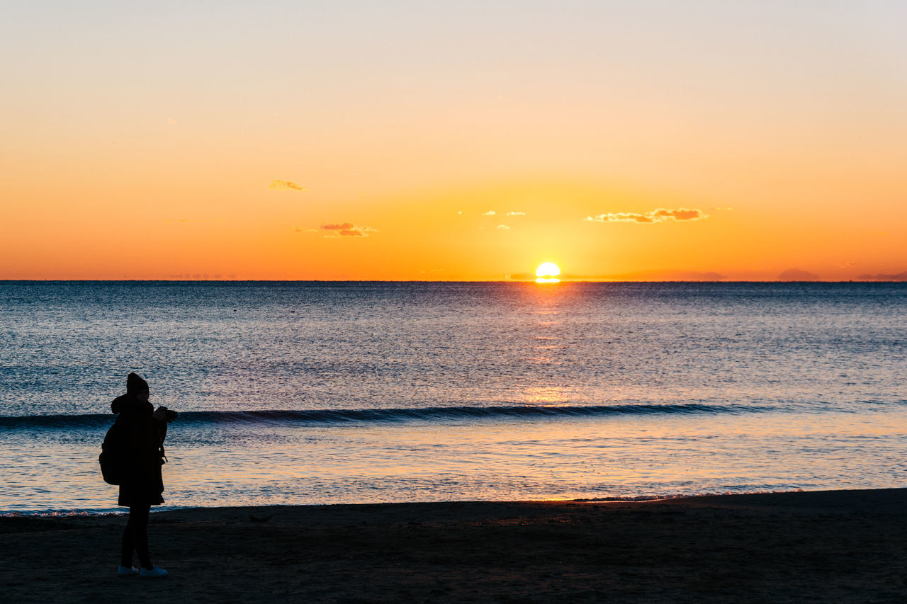 Woman Standing On Shore At Beach During Sunset