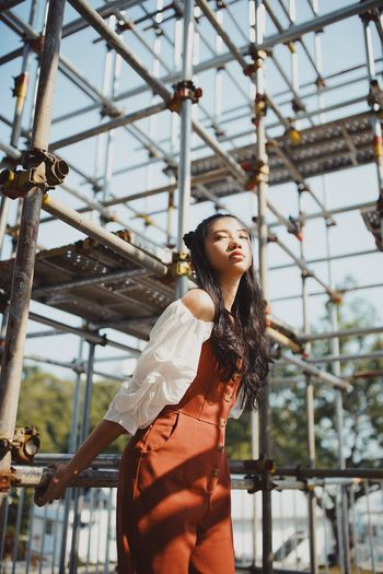 Young woman against scaffolding