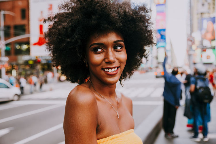 Thoughtful young woman with afro hairstyle at city street