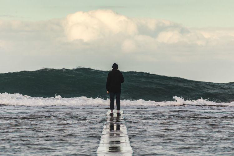 Rear View Of Man Standing On Groyne Over Sea Against Sky