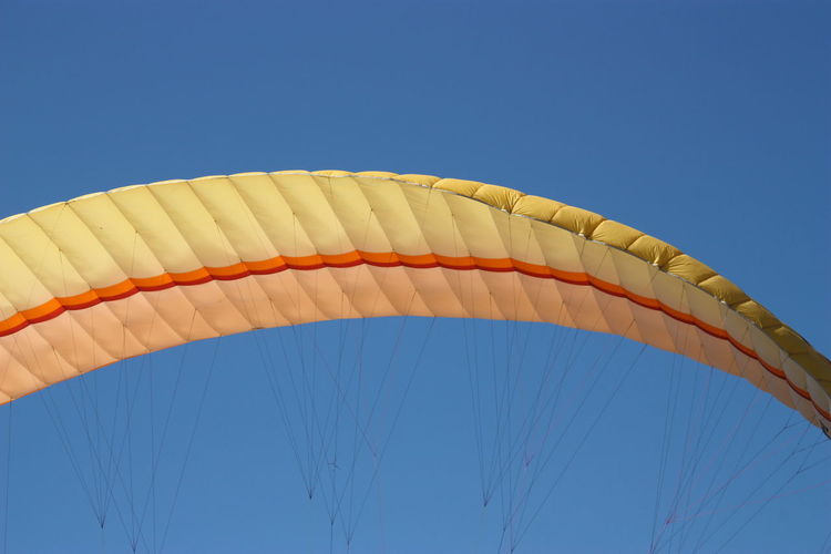 Low angle close-up of parachute against clear blue sky