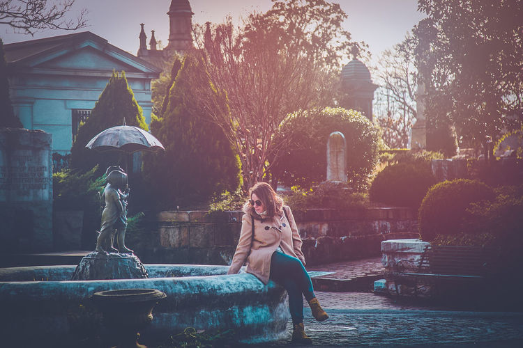 Cemetery Fountain Gothic Romantic Architecture Beautiful Woman Building Building Exterior Built Structure Full Length Garden Leisure Activity Lifestyles Nature One Person Outdoors Park Plant Real People Sitting Tree Water Women Young Adult Young Women