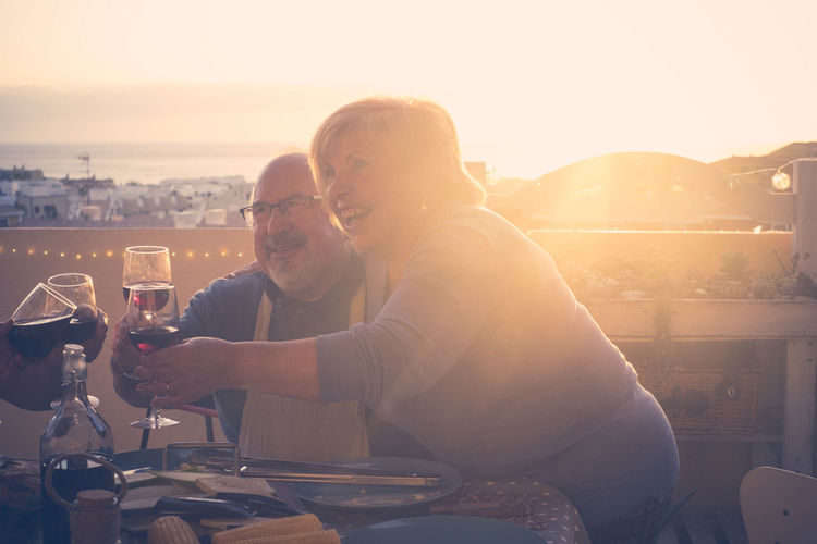 group of friends having dinner on the rooftop Woman Adult Bonding Celebration Cheerful Cityscape Day Drink Friendship Glass Bottle Happiness Love Men Outdoors People Retirement Senior Couple Sky Smiling Sunlight Sunset Togetherness Two People Wine Wineglass