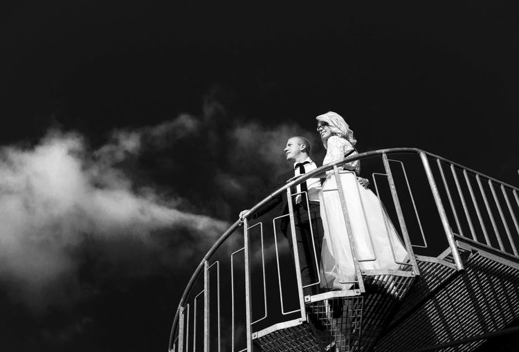 Low angle view of bridal couple standing on staircase against sky