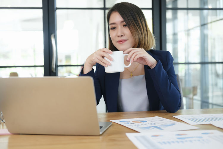 Young woman drinking coffee at table