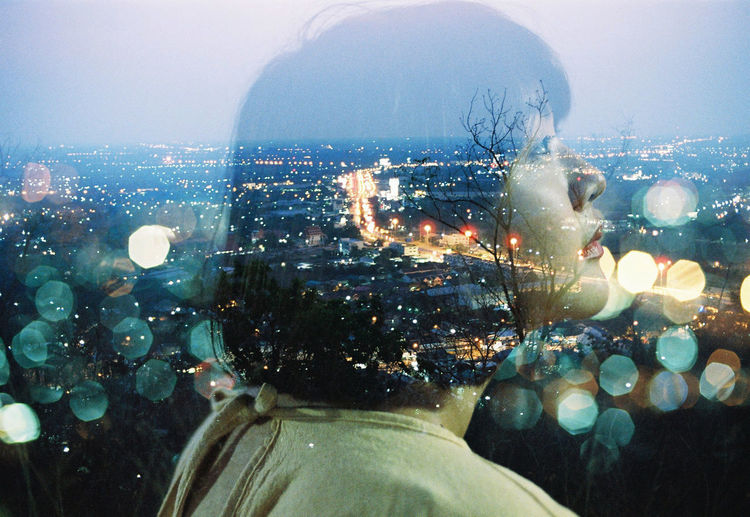 Rear view of man and cityscape against sky