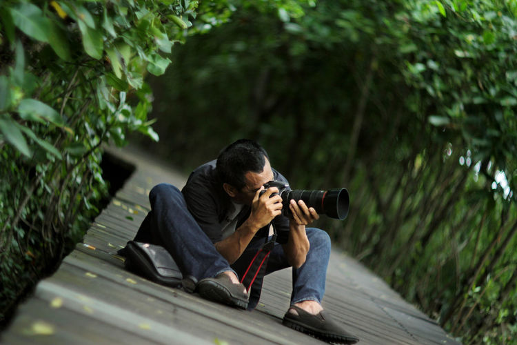 Man photographing while sitting by tree