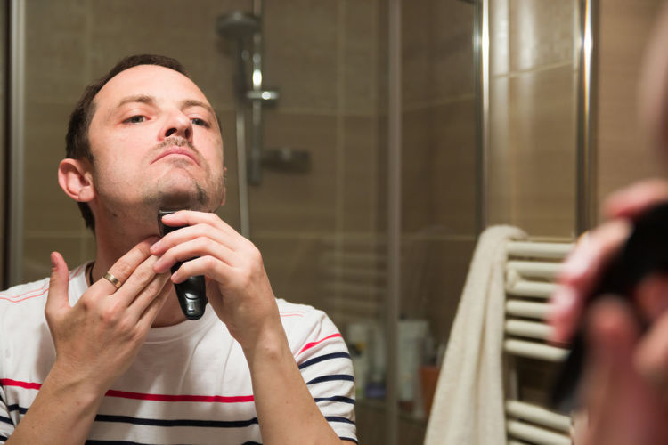 Reflection of man on mirror while trimming beard in bathroom
