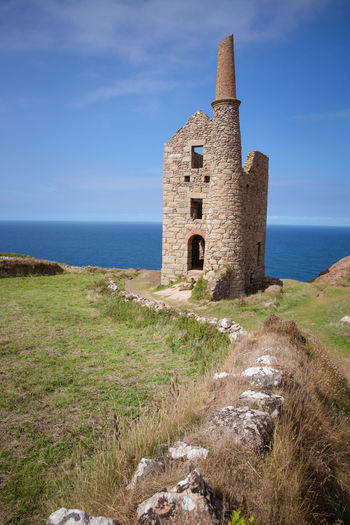 A derelict Cornish tin mine building along the coast of Cornwall, UK which is associated with the Poldark TV series Architecture Building Building Exterior Built Structure Cornwall Day Grass History Horizon Horizon Over Water Land Nature No People Old Outdoors Plant Poldark Ruined Sea Sky The Past Tin Mine Tower Uk Water
