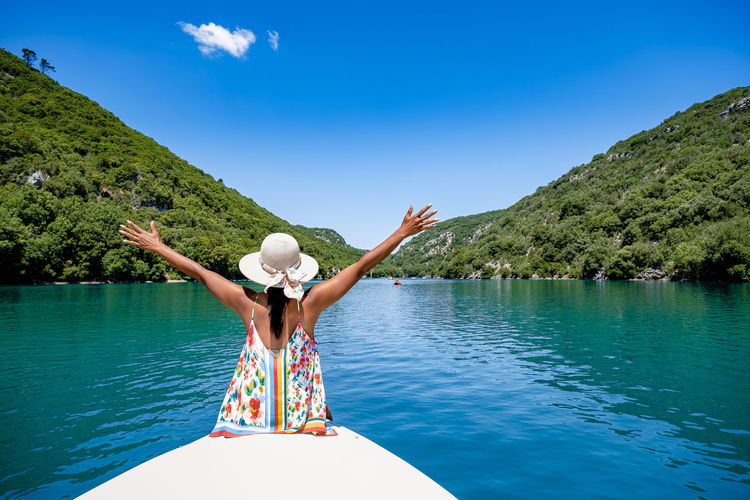 Rear view of woman sitting on boat in lake against sky