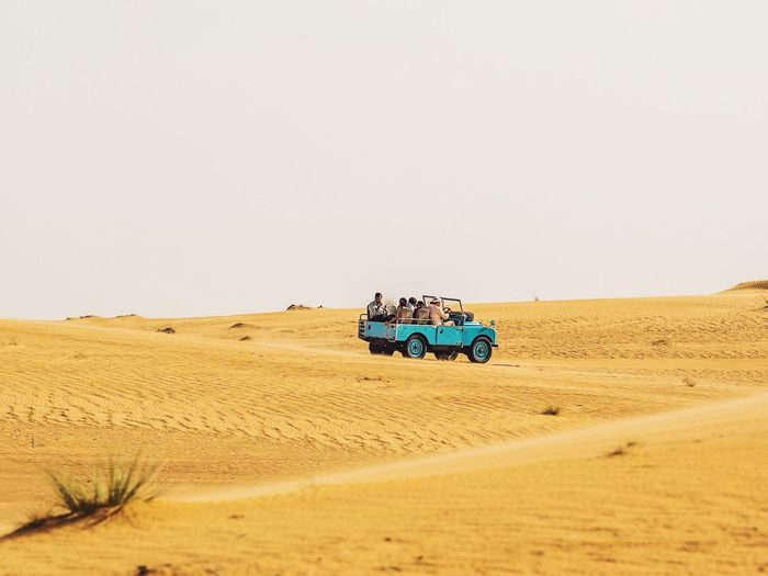People Traveling In Off-Road Vehicle On Desert Against Sky During Sunny Day