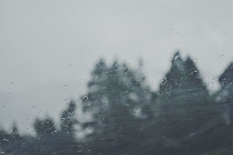 Man seen through wet window during rainy season