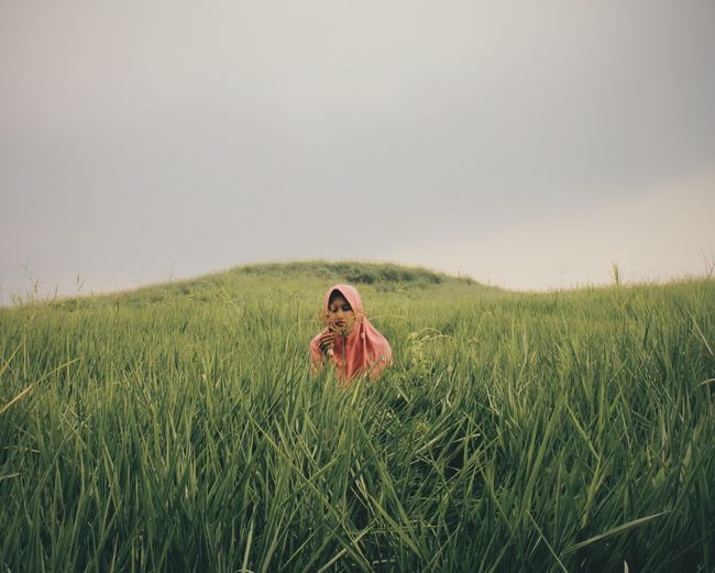 Woman in religious dress amidst grass at mountain against sky