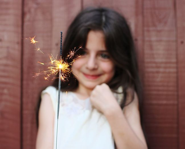 Close-up of smiling girl holding lit sparkler