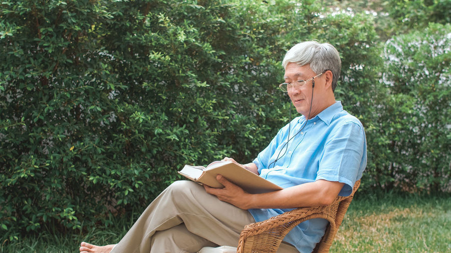 Side view of man reading book while sitting on chair against plants