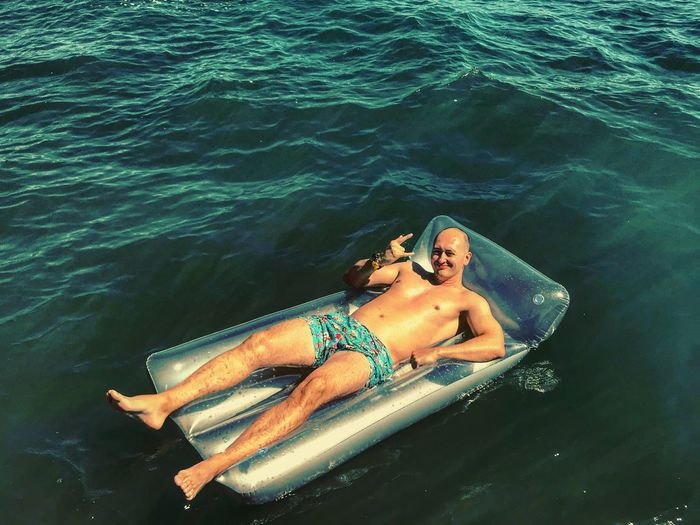 High angle portrait of shirtless mid adult man gesturing while lying on pool raft in sea