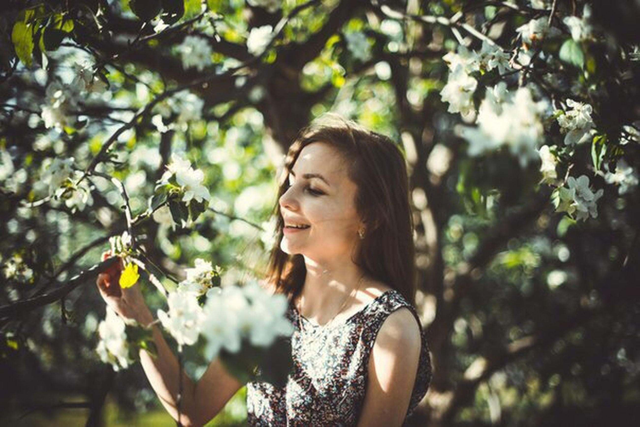 person, tree, young adult, focus on foreground, lifestyles, young women, portrait, leisure activity, headshot, front view, looking at camera, flower, branch, long hair, growth, nature