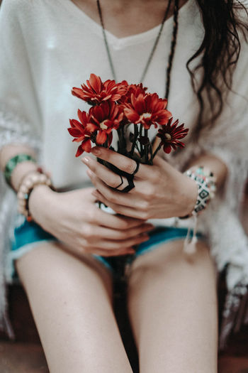 Female hands holding a bouquet of fresh red flowers. hippie summer concept