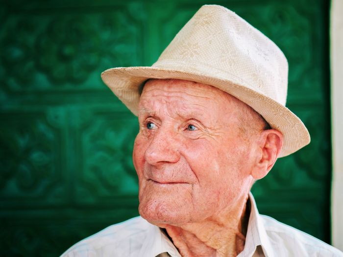 Close-up of thoughtful senior man wearing hat