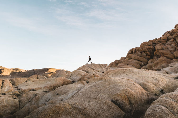 Low Angle View Of Man Walking On Rocky Mountain Against Sky