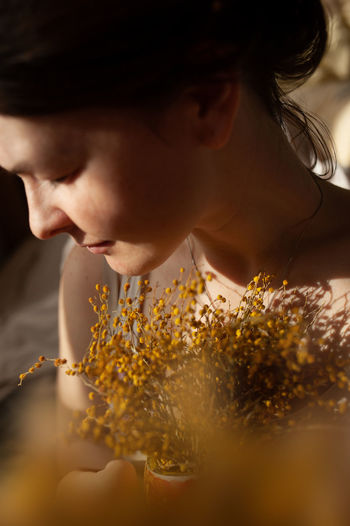 Sensual portrait of young woman looking down with mimosa flowers