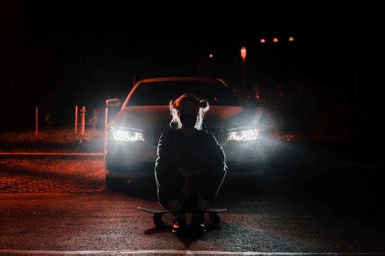 Rear view of man sitting on illuminated street at night