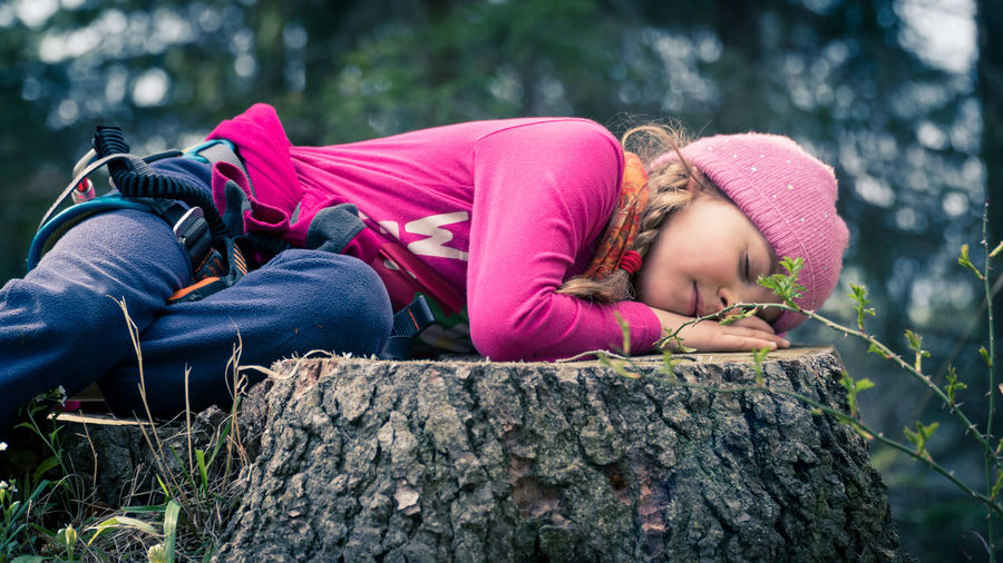 Cute little girl wearing purple blouse and pink hat sleeping on a cut tree trunk in a forest Day Nature One Person Outdoor Outdoors Resting Tired Tree Trekking