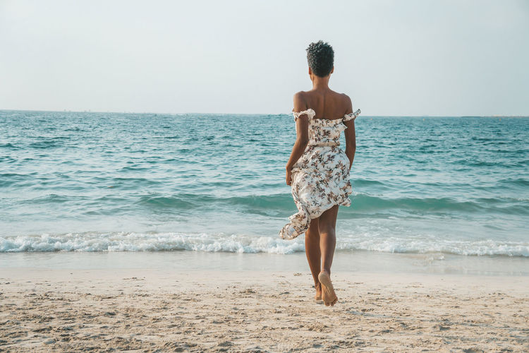 Full Length Rear View Of Woman Walking At Beach Against Clear Sky
