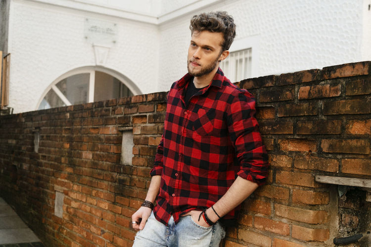Handsome Man Standing Against Brick Wall