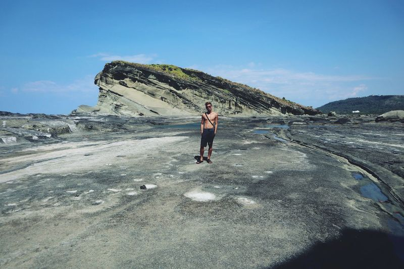 Full length of shirtless man standing on land against sky