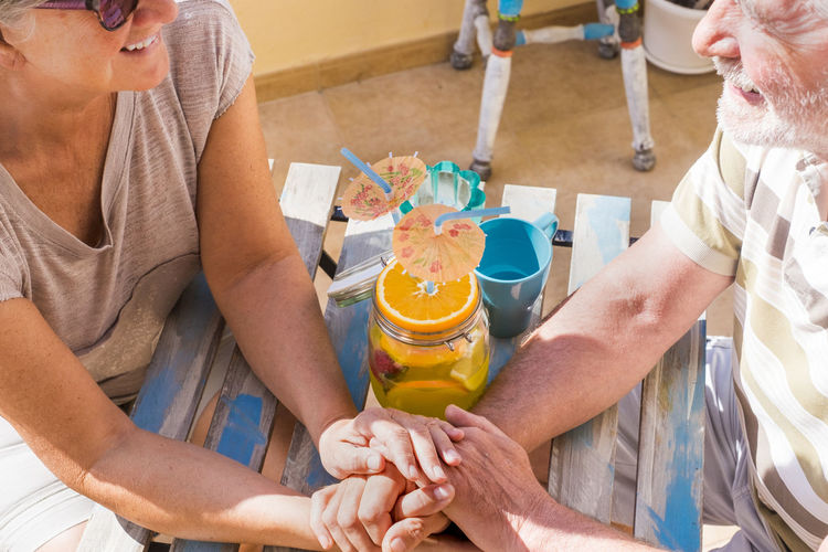 Midsection Of Senior Couple Holding Hands At Table In Balcony