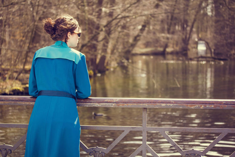 Rear View Of Woman In Blue Trench Coat Standing By Lake During Sunny Day