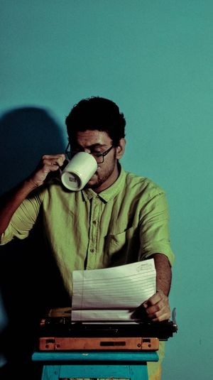 Young man drinking coffee while sitting against blue wall