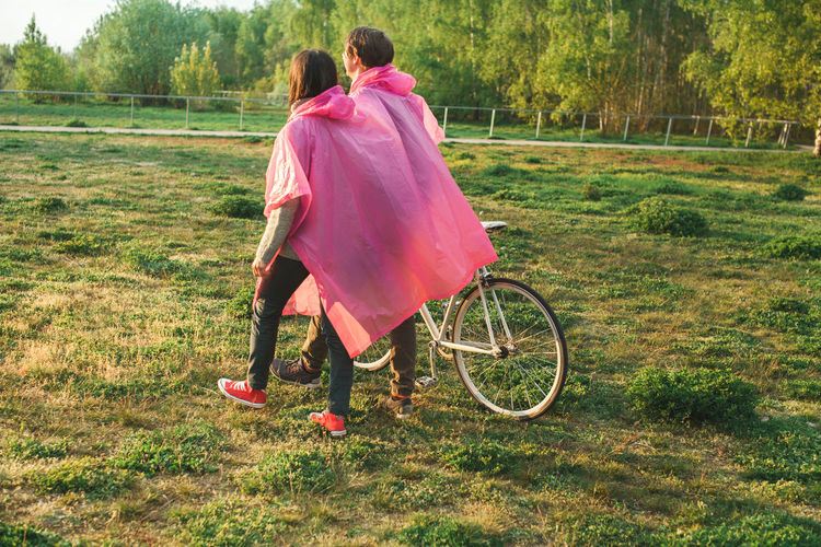 Couple wearing one piece two people rain poncho Pink Bycicle Day Full Length Grass Leisure Activity Lifestyles Nature Outdoors Park People Togetherness Two People Walking