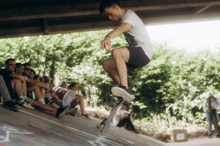 Side view of young man jumping outdoors