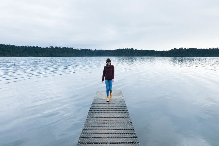 Young woman walking on jetty over lake