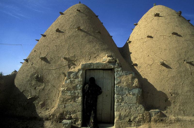 Woman entering abandoned adobe house