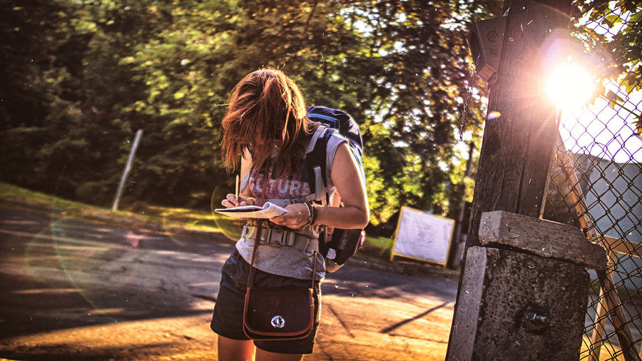 Woman writing in book while standing on road