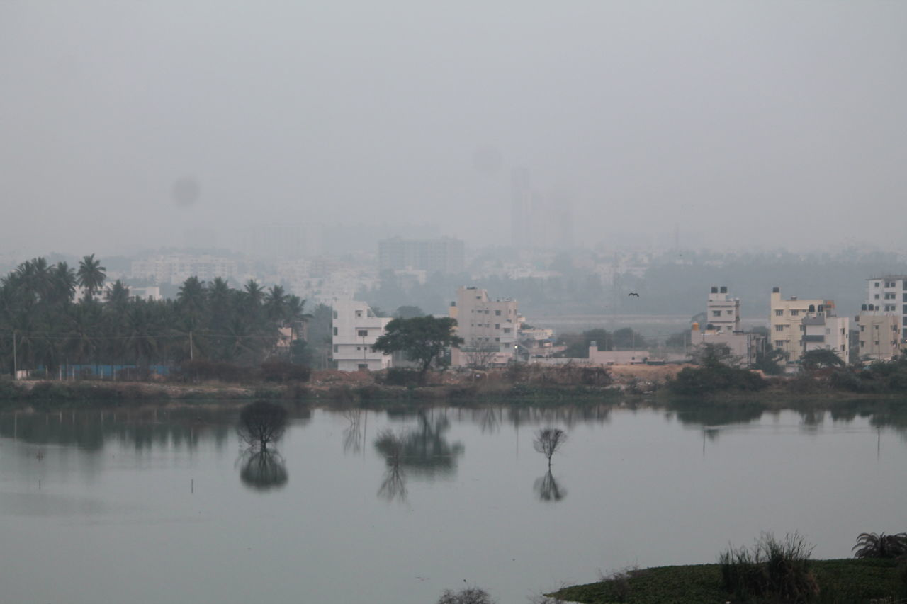 reflection, fog, water, no people, tree, nature, architecture, building exterior, outdoors, lake, day, built structure, sky, beauty in nature, city