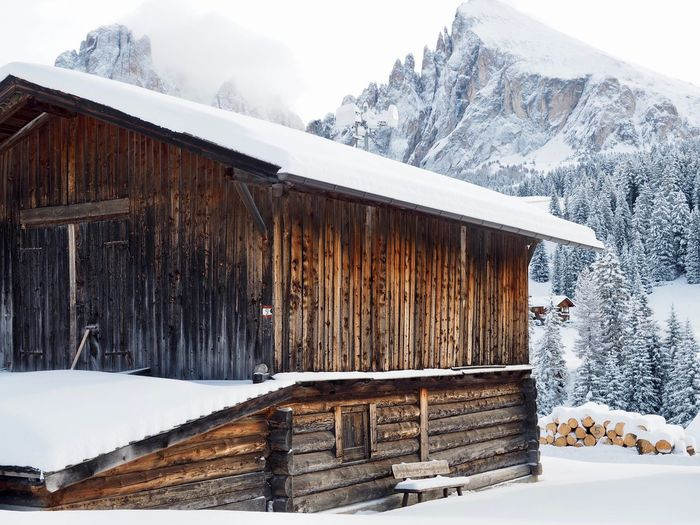 Wooden hut by snowcapped mountains against sky during winter