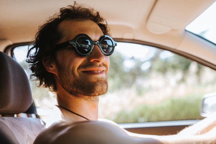 Close-up of smiling man sitting in car