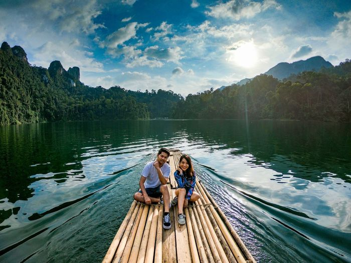 Couple sitting on wooden raft in lake against trees