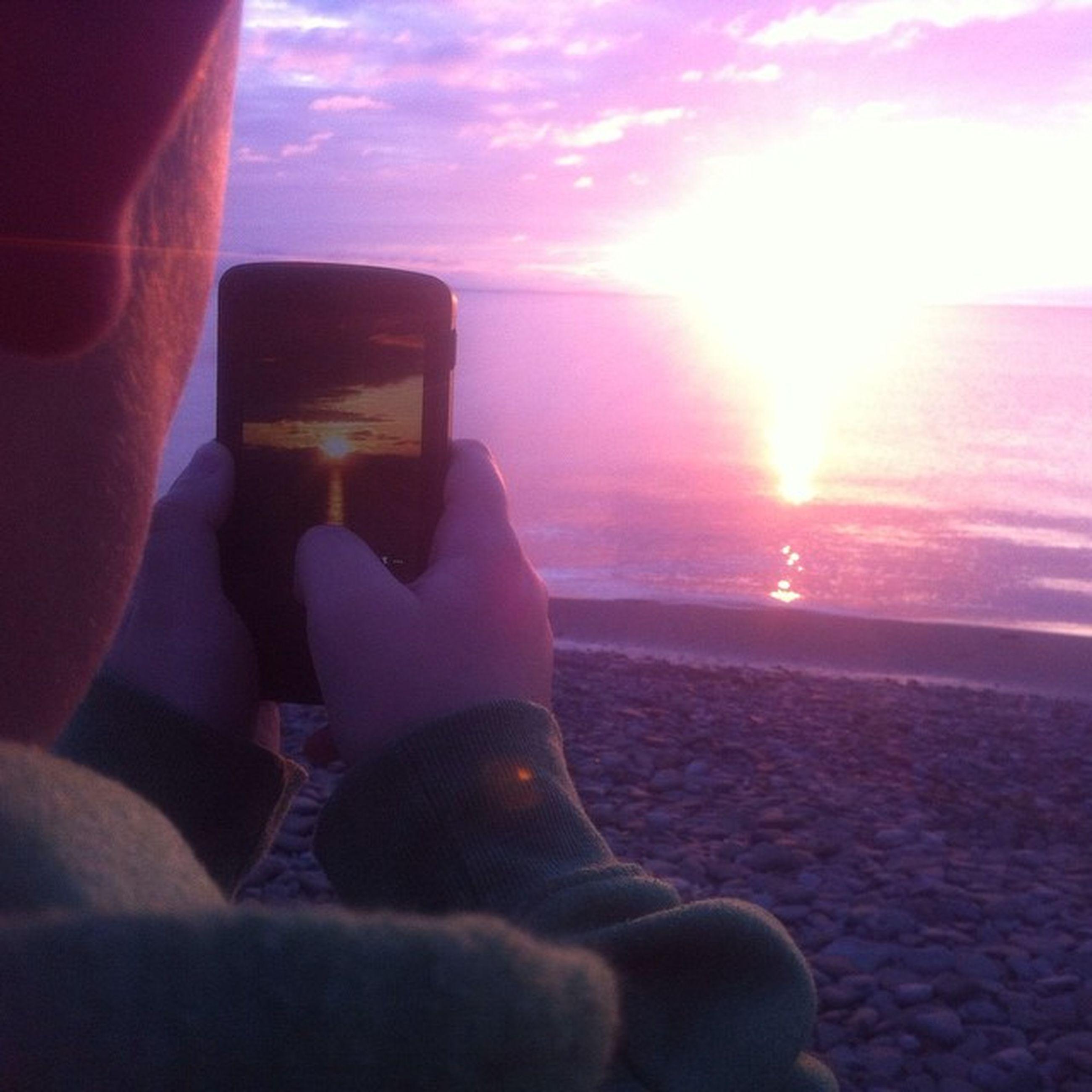 sun, lifestyles, sunset, sky, leisure activity, sunlight, sea, sunbeam, lens flare, part of, beach, horizon over water, person, cloud - sky, unrecognizable person, reflection