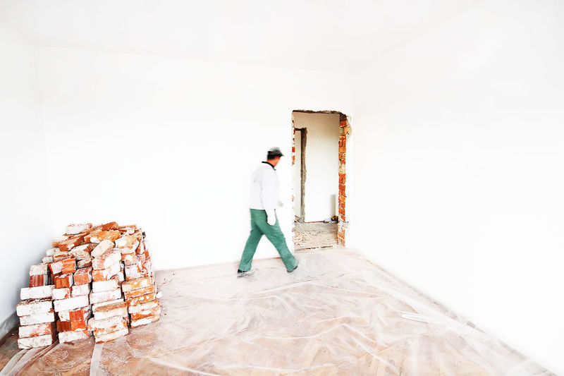 Man Walking By Wall Against Bricks At Home During Renovation
