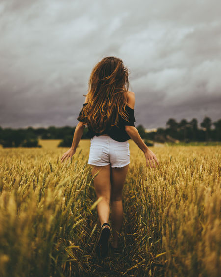 Rear view of woman standing in wheat field