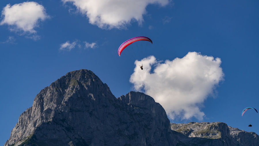Austria Adventure Beauty In Nature Cloud - Sky Day Exhilaration Extreme Sports Flying Formation Freedom Leisure Activity Low Angle View Mid-air Mountain Mountain Peak Mountain Range Nature Outdoors Parachute Paragliding Real People Rock Sky Sport Unrecognizable Person