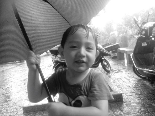 Rain on PIngjiang Road Suzhou, China little Boy Playing with Umbrella in his Wet clothes