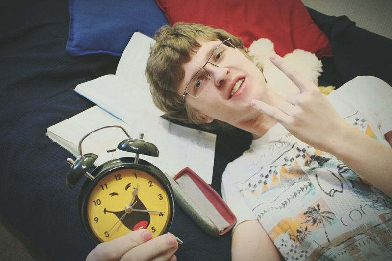 Portrait of teenage boy holding alarm clock while gesturing rock sign on bed at home